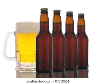 A frosty mug of beer behind a row of brown beer bottles. Horizontal format over white with reflection.