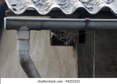frosty spider web on an old  drainpipe in winter