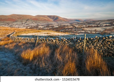 A frosty winter sunrise in the Yorkshire Dales featuring a typical farmers stone wall. The Howgill Fells sit in the background