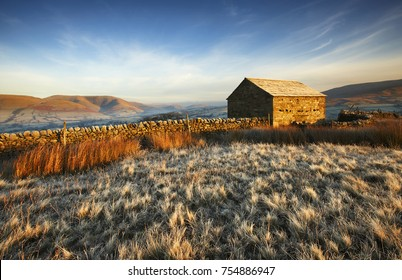 A frosty winter sunrise in the Yorkshire Dales featuring a typical farmers stone barn. The Howgill Fells sit in the background shrouded in a faint mist.