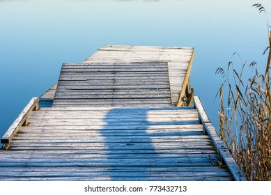 Frosty wooden pier sided by reed and windless sea. Windless water in background.