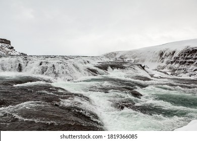 Frothing waters of Gullfoss Waterfall surrounded by snow-covered rocks, Golden Circle Route, Iceland