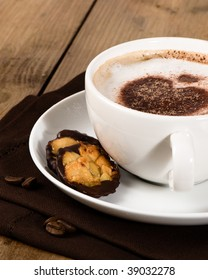 Frothy cappuccino with florentine biscuits on wooden table