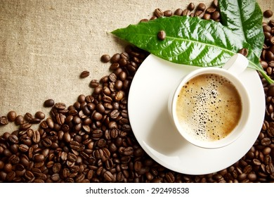 Frothy coffee cup and coffee beans at the bottom horizontal on flax material with green coffee leaf