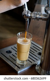 Frothy fresh nitro coffee from the tap,barista make from roasted bean coffee