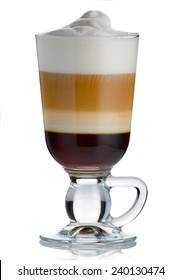 Frothy, layered cappuccino in a clear glass mug with cinnamon sprinkled isolated