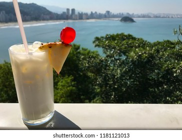 A frothy pina colada drink sits on a ledge overlooking a beautiful Brailian coastline