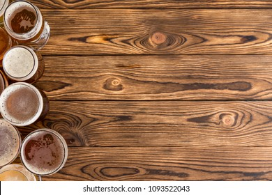 Frothy pints of beer on a rustic timber bar top with copy space.