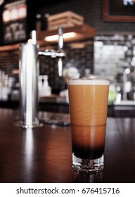 frothy sparkling nitro cold brew ready to be served at coffee shop bar environment background. coffee machine wooden table