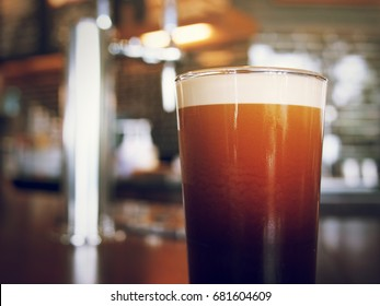 frothy sparkling nitro cold brew ready to be served at coffee shop bar environment background. coffee machine wooden table vivid colorful vintage