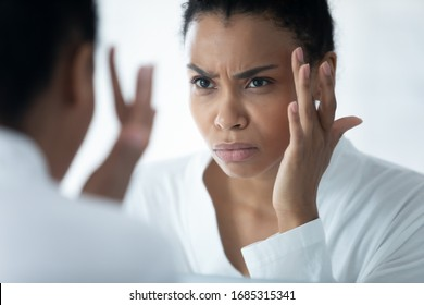 Frown African woman wear white bathrobe looking in mirror see first mimic wrinkles feels stressed, face skin lose elasticity changes after 30s, aging process, need cosmetology facial treatment concept