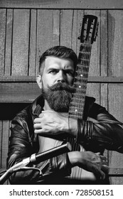 Frown bearded man with beard moustache and gray hair stylish hipster biker male with guitar outdoors on wooden background