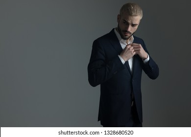 frown blonde man in suit adjusting his buttons on his shirt