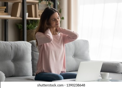 Frown woman sitting on couch near computer take break touches her neck suffers from painful feelings ache caused by poor wrong posture, sedentary work, sitting at laptop for long period concept image