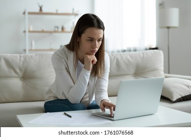 Frown young woman sit on couch feels tired exhausted after long usage of laptop looks at pc screen experiencing difficulties in bank application applying, search for right information having troubles