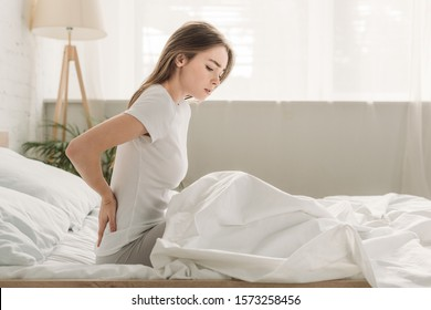 frowned girl touching loin while sitting in bed and suffering from pain
