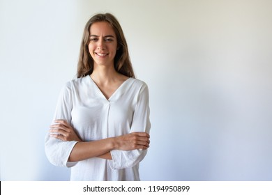 Frowning attractive student girl in white blouse crossing arms and looking at camera. Portrait of smiling skeptical lady with furrowed eyebrows. Mistrust concept