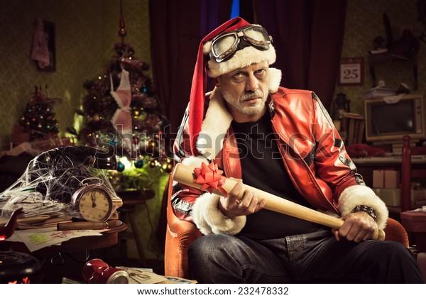 Frowning Bad Santa with baseball bat gift looking at camera