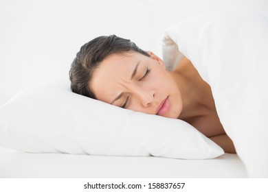 Frowning casual brunette having a nightmare in bright bedroom
