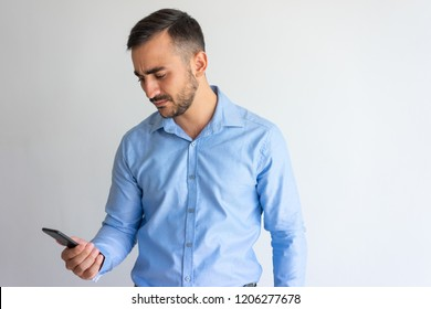 Frowning concerned businessman focused on phone screen. Puzzled young man using smartphone. Communication or bad news concept