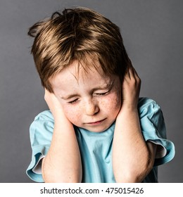 frowning little boy closing his ears and eyes against domestic violence or education, afraid of relationship problems, grey background, contrast effects