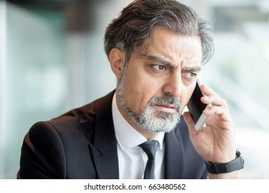 Frowning man in suit having phone conversation
