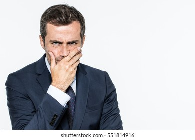 frowning unhappy middle aged businessman thinking with hand on mouth, expressing corporate doubts and concerns, copy space, white background studio