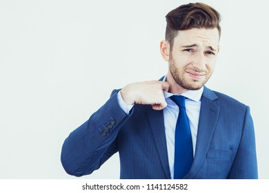 Frowning young businessman taking off tie and looking at camera. Gloomy male manager tearing away tie which suffocating him. Exhausted man concept