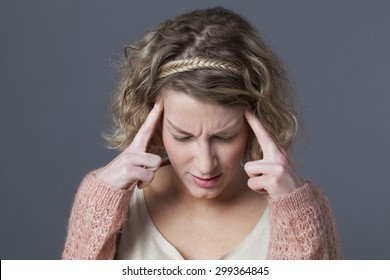 frowning young girl with curly blonde hair and pink sweater looking down with hands on temples for seeking for concentration or fighting against migraine