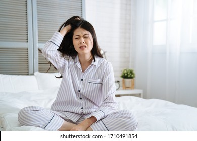 frowning young girl feeling tired doesn't want wake up in the morning. unhappy lady with hand scratching hair with itch head. exhausted asian japanese woman mad sitting on bed in bright bedroom.