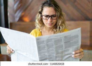Frowning young woman reading job ads in newspaper. Displeased girl reading article in local newspaper in morning. Bad news concept