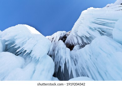 Frozen Baikal Lake. Bottom view on beautiful ice-covered rocks on Olkhon Island with long icicles against the blue sky. Natural unusual background. Winter travel and fun holidays