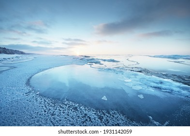 Frozen Baltic sea shore at sunset. Ice fragments close-up, snow-covered pine forest in the background. Colorful cloudscape. Symmetry reflections on the water. Nature, climate change. Panoramic view - Shutterstock ID 1931142059