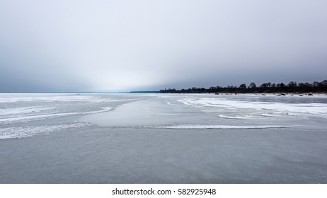 frozen beach in cold winters day with colorful sky and ice