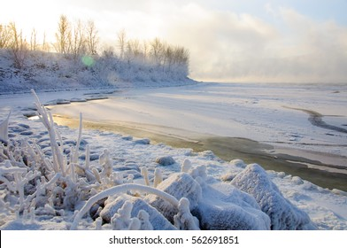 Frozen beauty of winter landscape. Sun going down the horizon. Rocks on the bank of the river. Sparkling snow in last beams of the day.