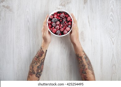 frozen berries, black currant, red currant, raspberry, blueberry. top view in a vintage ceramic white bowl on rustic wooden table isolated. Two old school tattooed men hands holds pot