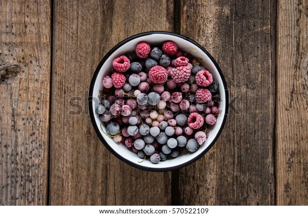 gefrorene Beeren, schwarzer Johannisbeere, roter Johannisbeere, Himbeere, Heidelbeere in Emaille auf Holztisch im rustikalen Stil, Draufsicht.