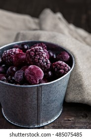 Frozen berries mix in a black bowl on wooden background. Still life photography
