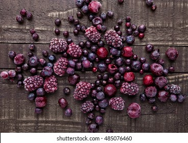 Frozen berries mix on wooden background. Still life photography