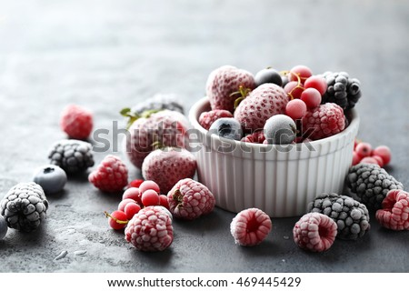 Frozen berries on a black wooden table