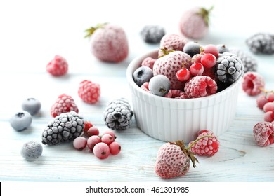 Frozen berries on a white wooden table