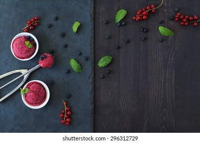 Frozen berries sorbet with fresh mint leaves in two white bowls and an ice cream scoop. Served on a stone slate over a wood, black background.
