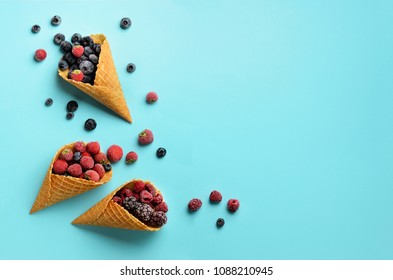 Frozen berries - strawberry, blueberry, blackberry, raspberry in waffle cones on blue background. Top view. Banner. Pattern for minimal style. Pop art design, creative concept