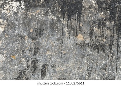 Frozen black spots and vertical streams of bitumen on a concrete wall. Grunge texture of the old dark surface that is covered with bitumen.