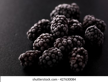 frozen blackberries on a black stone kitchen table