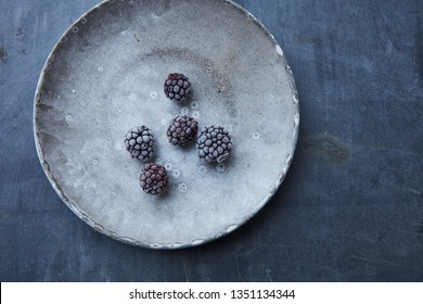 Frozen blackberries on a frosty plate