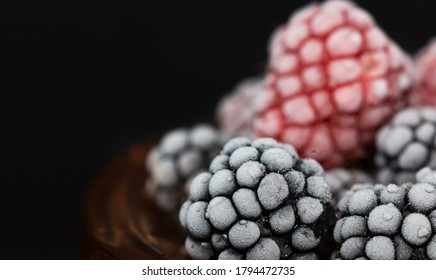 Frozen blueberries and raspberries close up picture. Berries in hoarfrost are on the black background. Ingredients for making desert. Card for restaurant.