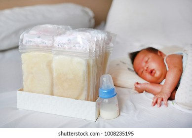 Frozen breast milk in plastic bag on the bed with infant baby sleeping.