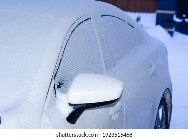 Frozen brilliant shimmering snow at night side window and rear view mirror of the car