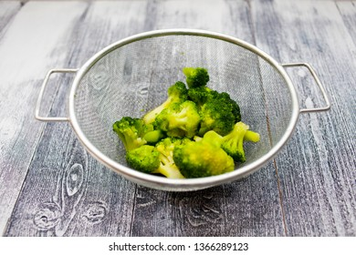 Frozen broccoli in a colander, on a wooden background. Healthy diet. Colander with fresh green broccoli on table